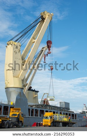 Cranes unloading a ship in a harbor - stock photo