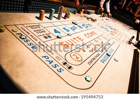 Craps Table, Chips Piles and People Gambling all Around - stock photo
