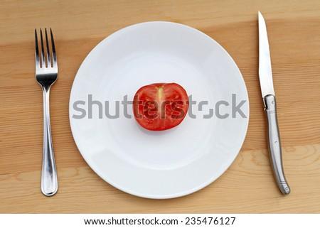 Crash diet concept shot.  Half tomato on plate. - stock photo