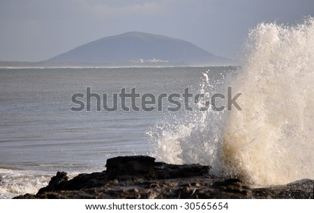 crashing wave and mountain in background - stock photo