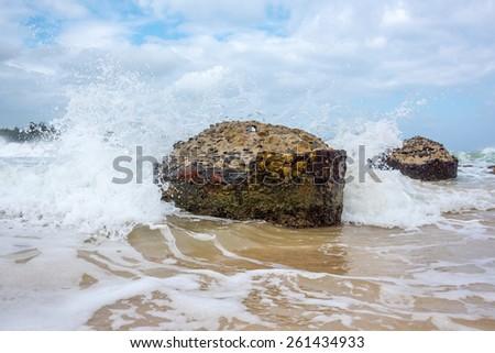 Crashing wave upon old weathered pier pillar - stock photo