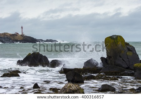 Crashing waves in the foreground of the Cape Forchu lighthouse in Yarmouth, Nova Scotia, Canada. - stock photo