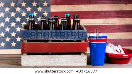 Crate of beer and party stuff for Fourth of July celebration with vintage wooden USA flag in background. - stock photo
