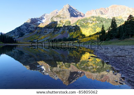 Crater Lake with Autumn Colors and reflection of Maroon Bells in morning light, Aspen, Colorado - stock photo