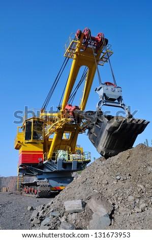crawler-mounted excavator extract  iron ore in opencast mine on blue sky background - stock photo