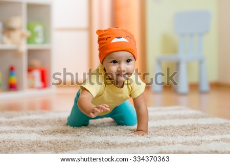 crawling baby boy at home on floor - stock photo