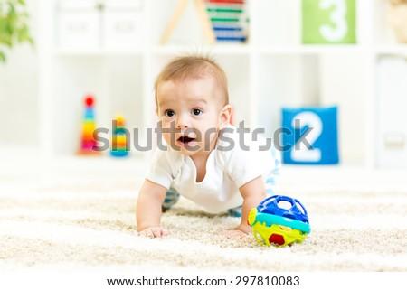crawling funny baby boy indoors at nursery - stock photo