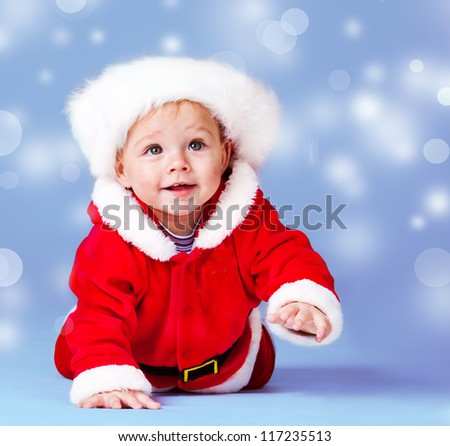 Crawling sweet Santa helper over blue snowy background - stock photo
