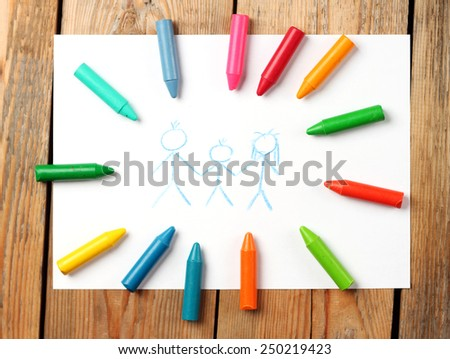 Crayons lying on a paper with children's drawing family. Selective focus, top view - stock photo