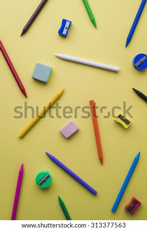 Crayons, pencil sharpeners and erasers of different colors on a yellow background - stock photo