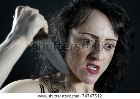 crazed woman stabbing with a large kitchen knife - stock photo