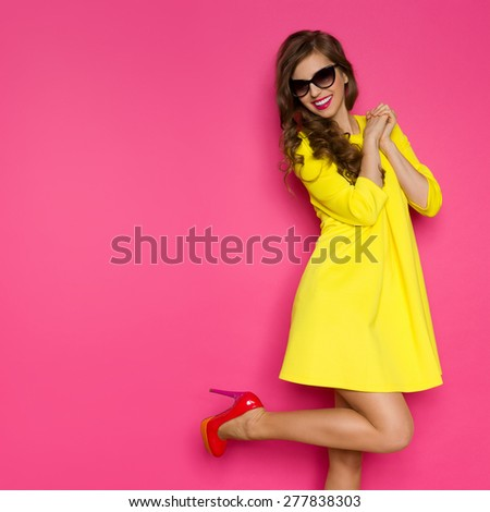 Crazy About New Shoes. Excited girl in yellow mini dress posing on one leg against pink background. Three quarter length studio shot. - stock photo