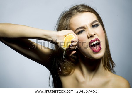 Crazy blonde girl portrait with bright make up looking forward holding half of fresh juicy orange standing on gray background copyspace, horizontal picture - stock photo