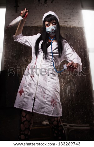 Crazy dead nurse with knife in the hand in a dark room - stock photo