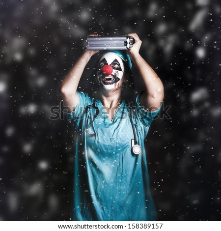 Crazy doctor clown standing in falling rain with first aid kit. Health crisis joke - stock photo