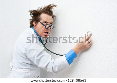Crazy doctor listening to the stethoscope - stock photo