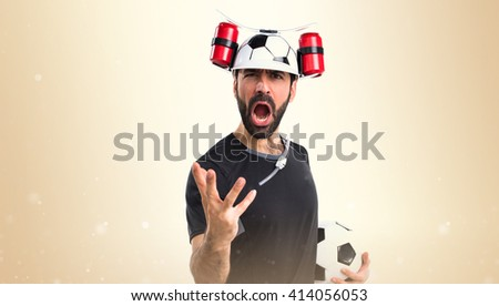 Crazy football player doing surprise gesture - stock photo