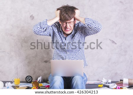 Crazy frustrated businessman with laptop sitting on messy office desktop and pulling his own hair - stock photo