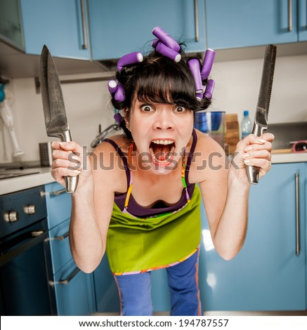 Crazy funny housewife in an interior of the kitchen - stock photo