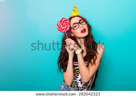 Crazy funny pretty woman posing against blue wall wearing trendy summer  outfit , cool cute glasses and party hat. Holding big pink lollypop .  - stock photo