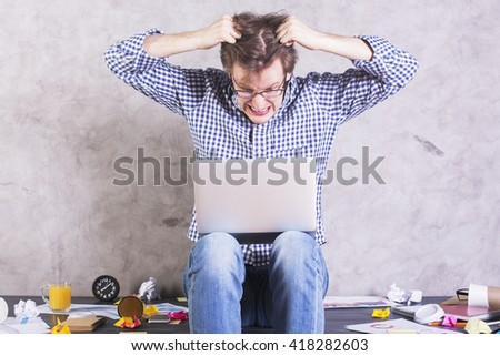 Crazy furious man with laptop sitting on messy office desktop and pulling his own hair. Psycho man losing it at workplace. Man getting frustrated after reading e-mail on laptop - stock photo