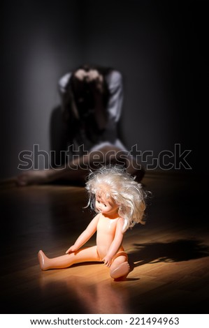 Crazy girl and plastic doll on the floor - stock photo