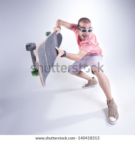 crazy guy with a skateboard making funny faces - stock photo