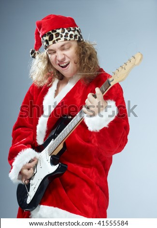 Crazy man in the red Santa Claus costume playing the guitar rock music. Christmas theme - stock photo