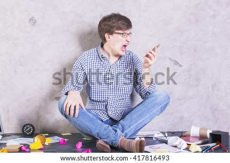 Crazy man sitting on messy desktop and screaming into phone. Furious guy getting mad at colleague over mobile phone. Frustrated man yelling at subordinate through phone - stock photo