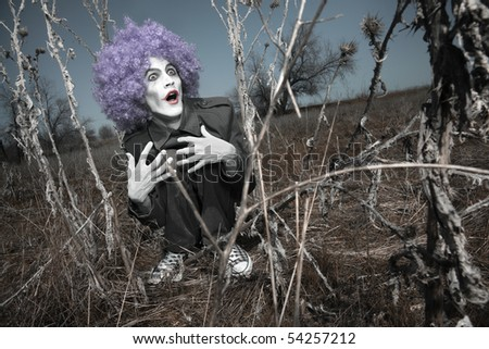 Crazy maniac clown outdoors hidden in the thorns. Artistic colors added - stock photo