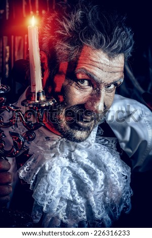 Crazy old man medieval scientist working in his laboratory. Alchemist. Halloween. - stock photo