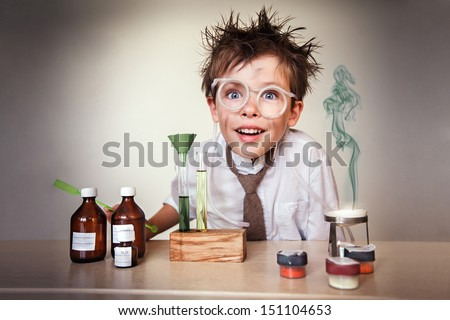 Crazy scientist. Young boy performing experiments - stock photo