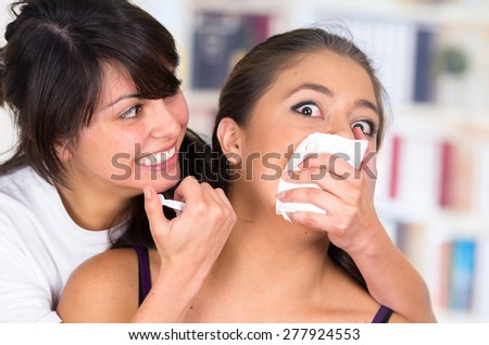crazy woman injecting young scared girl with a syringe on the neck - stock photo
