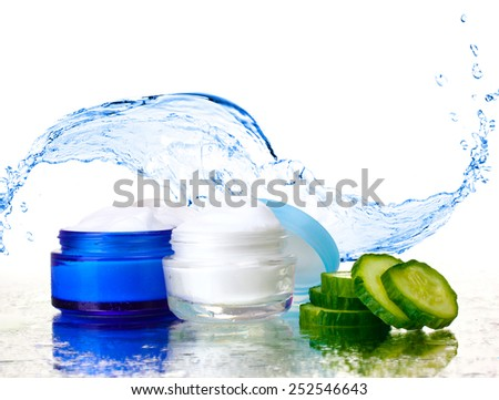 Cream and fresh sliced cucumber on mirror surface on abstract water splashing background - stock photo