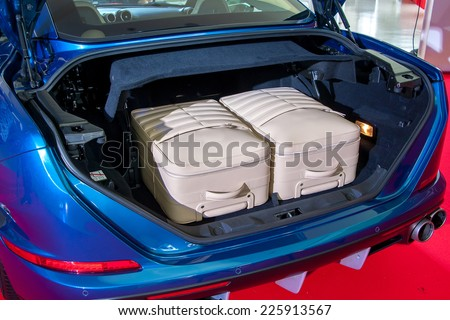 Cream big luggage inside the trunk of blue car - stock photo