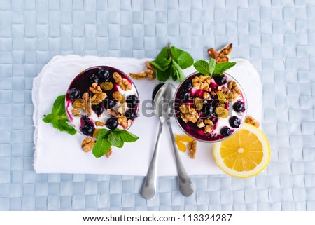 cream dessert with berries, black currant jam and nuts decorated with mint leaves - stock photo