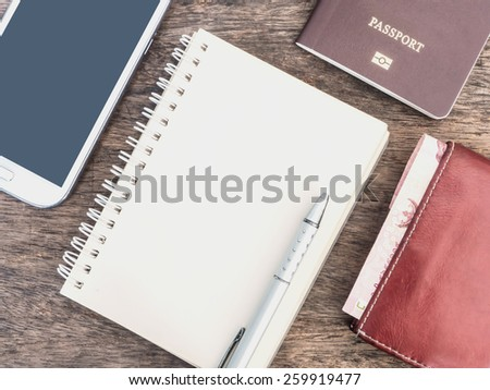Cream notebook, mobile phone, purse and passport on wood desk - stock photo