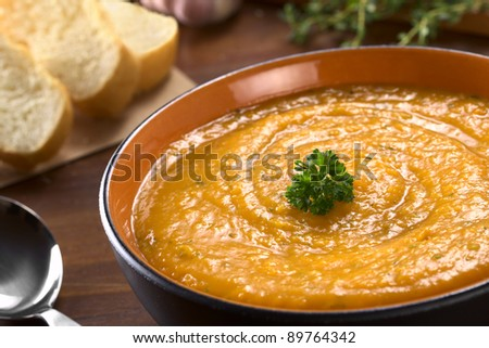 Cream of sweet potato prepared with garlic, thyme and basil, garnished with fresh parsley (Selective Focus, Focus on the parsley) - stock photo