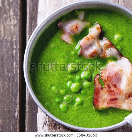 Cream soup of green peas in aluminum plate with fried bacon. Over old wooden table. Top view. Rustic style. Square image with selective focus - stock photo
