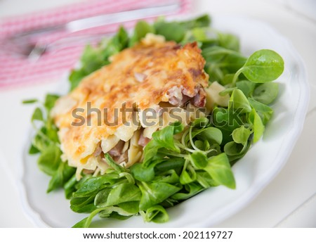 Creamy baked pasta with bacon and cheese and green salad - stock photo