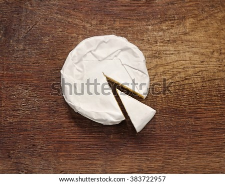 Creamy Brie on rustic wooden background, top view - stock photo