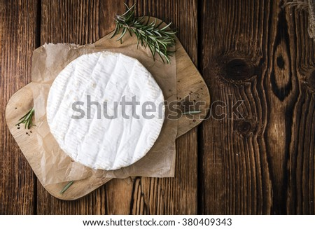 Creamy Camembert (close-up shot) on wooden background - stock photo