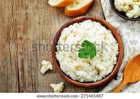 creamy cauliflower garlic rice on a dark wood background. the toning. selective focus - stock photo