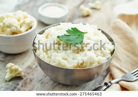 creamy cauliflower garlic rice on a white wood background. the toning. selective focus - stock photo