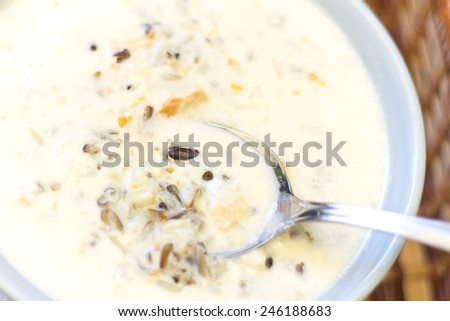 Creamy Chicken and Wild rice soup in a basket with bread for dipping - stock photo