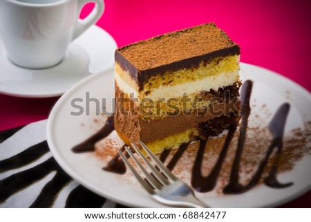 Creamy chocolate mousse cake on a white plate with a pink background. Added vignetting and very shallow depth of field. - stock photo