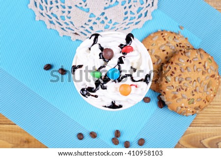 Creamy cocktail with waffles and chocolates next to the cookies on the table, top view. Tasty and nutritious dessert. Coffee latte with cream and sweets - stock photo