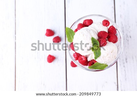 Creamy ice cream with raspberries on plate in glass bowl, on color wooden background - stock photo