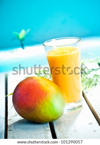 Creamy mango smoothie with blended fresh mango juice and yoghurt served overlooking a tropical ocean - stock photo