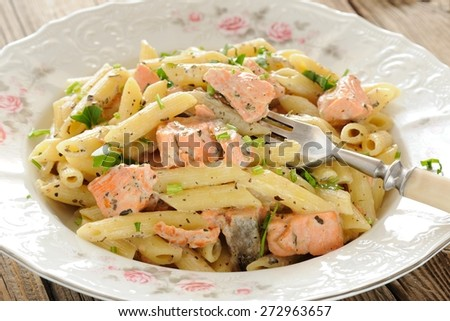 Creamy pasta with salmon and parsley in white plate - stock photo
